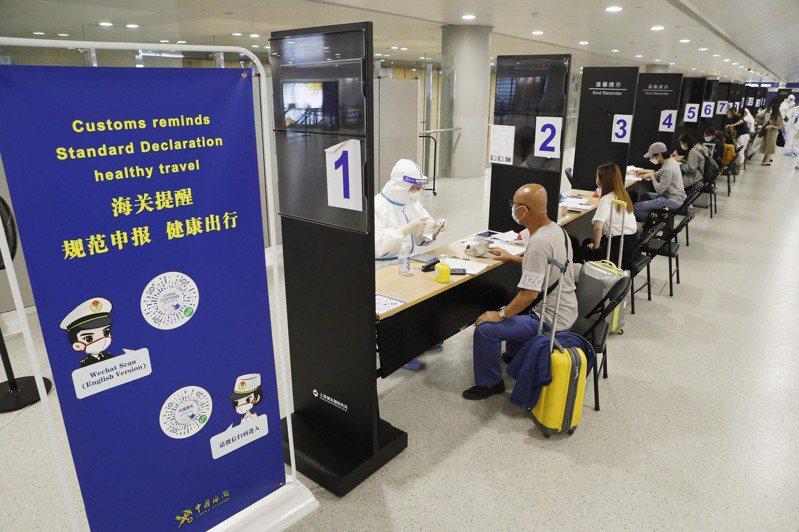 透過入境普篩,上海20日報告11例境外移入新冠肺炎確診病例。圖為上海浦東機場逐一核實入境旅客信息。中新社