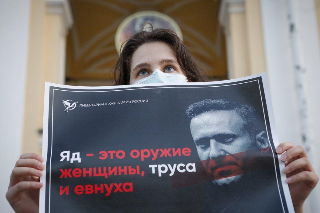 俄國聖彼得堡一名示威者高舉宣稱納瓦尼疑似遭下毒的海報。美聯社