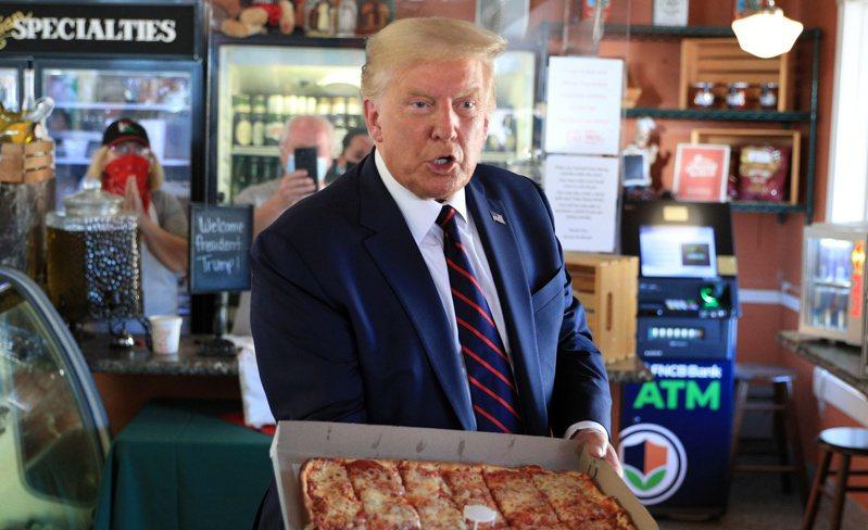 川普總統20日在賓州斯克蘭頓批評白登「拋棄」賓州,也批評白登是激進左派運動的傀儡,將伺機摧毀美國的生活。圖為他在當地一家披薩店買披薩。(路透)