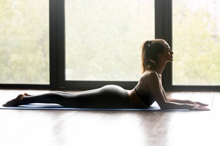 Young sporty woman practicing yoga, doin...