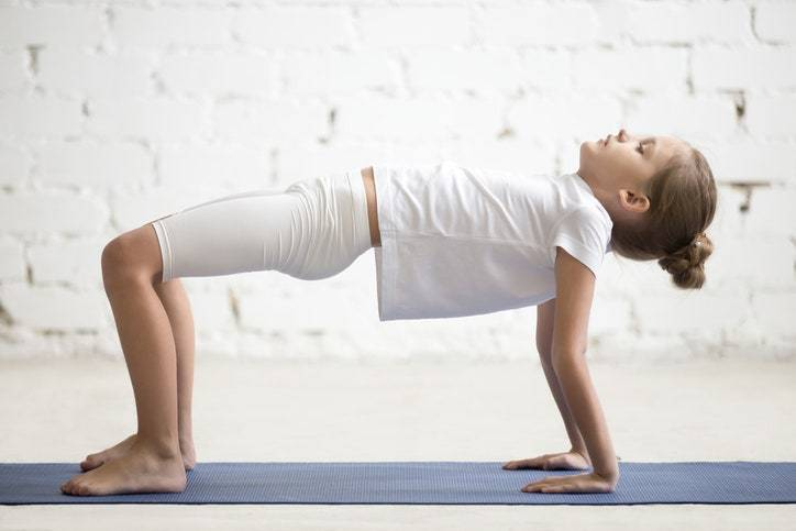 Serious girl child practicing yoga, stan...