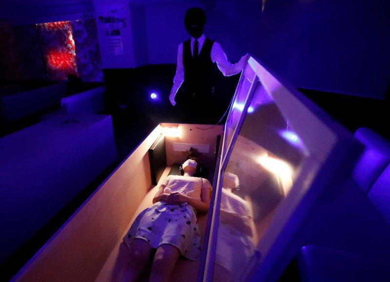 日本鬼屋和恐怖活動策劃公司「驚嚇團隊」試圖藉由讓民眾躺在棺材裡聽鬼故事,或被一群工作人員扮演持電鋸的殭屍圍繞,紓解新冠肺炎防疫壓力。(路透)