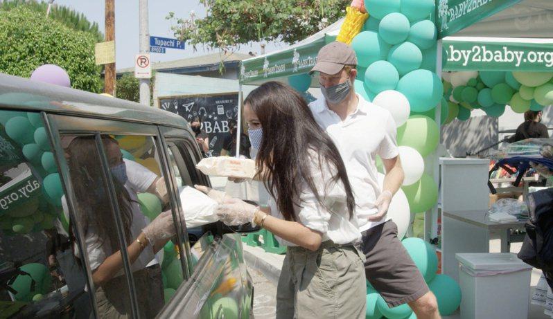 哈利與梅根19日在洛杉磯參加小學開學日慈善活動,幫校方把開學用品送入家長車內,家長不必下車領取。(路透)