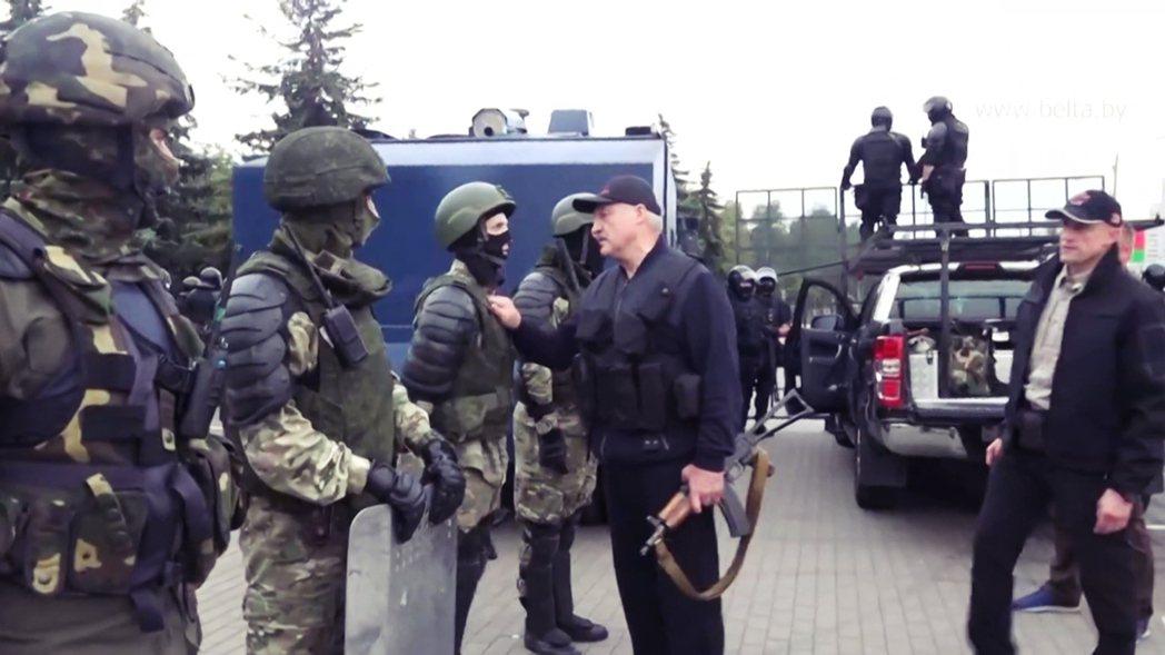 盧卡申科之後在軍警護航下走出總統府,並在軍警封鎖線向「忠誠愛國者們致意」。 圖/...