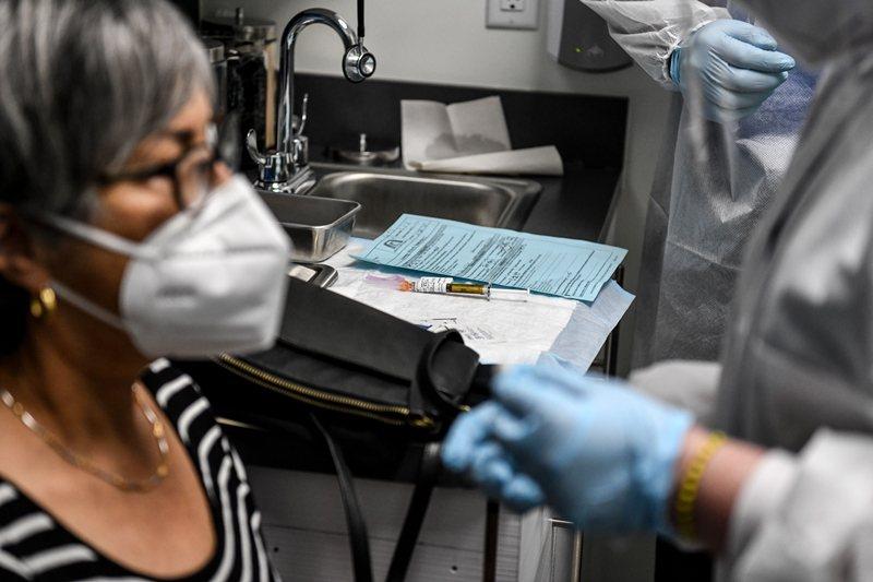 除了疫苗的效力,讓多少人接種亦是關鍵。 圖/法新社