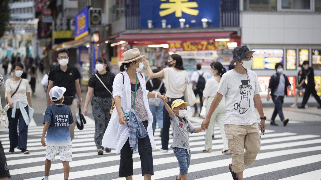 日本民眾十七日戴著口罩經過東京新宿街頭。 (美聯社)