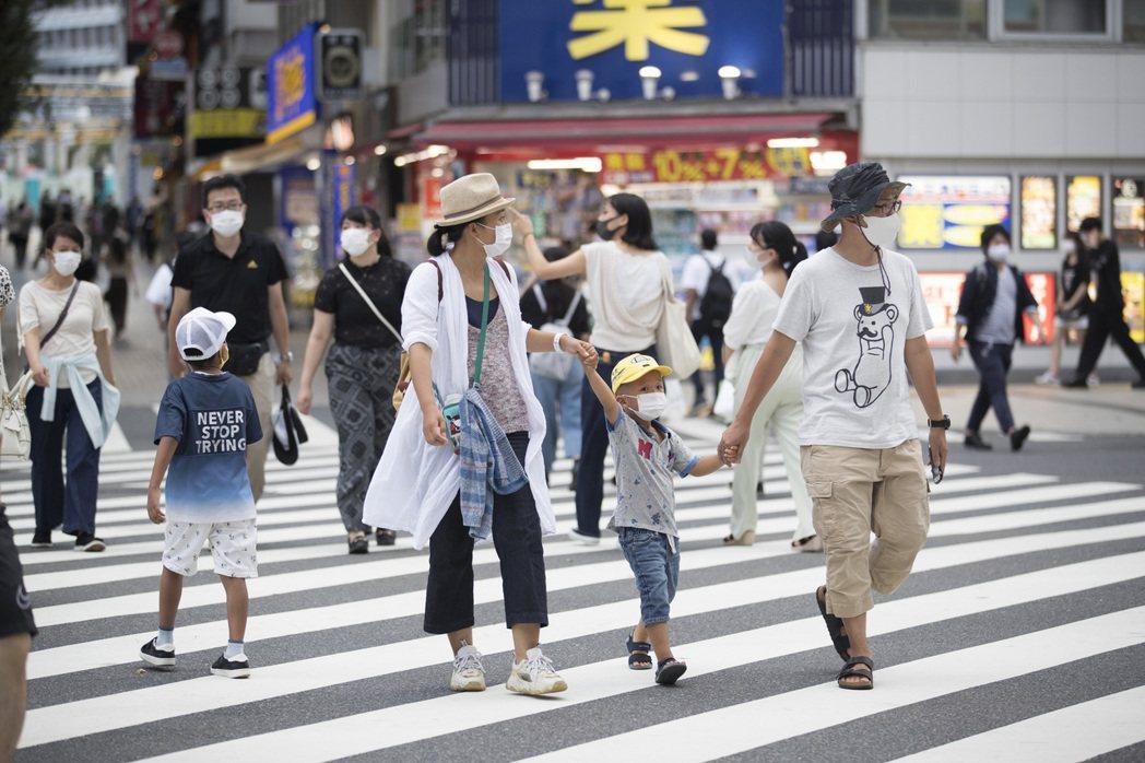 日本民眾戴著口罩經過東京新宿街頭。(美聯社)