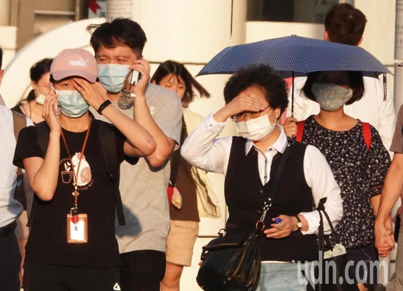 雙北等13縣市今天出現高溫,街頭上與多民眾遮擋刺眼陽光。記者潘俊宏/攝影