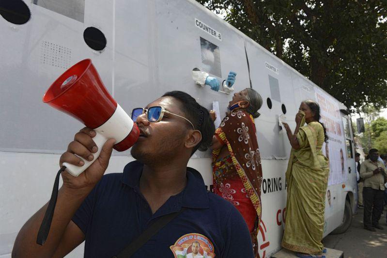 印度中部海德拉巴市一名志工5日用大聲公告訴居民,趕快到新冠病毒免費檢測車做檢測。法新社