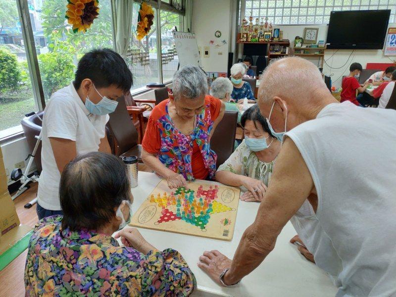 嘉義基督教醫院暑假與雙福基金會合作辦「銀響夏令營」,長者與學童們一起玩桌遊。 圖...