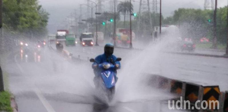 高雄市小港區沿海路部分慢車道積水較深,機車經過,水花四濺,騎士格外小心。記者楊濡嘉/攝影