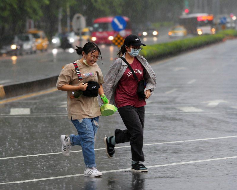 受到西南風影響及對流雲系統發展旺盛影響,大台北地區今天下午下起大雨,沒有攜帶雨具的民眾在雨中奔跑。記者林澔一/攝影