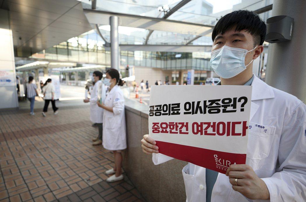 參與罷工的南韓醫生手持寫有「公共醫生增援?重要的是工作條件」的標語。 美聯社