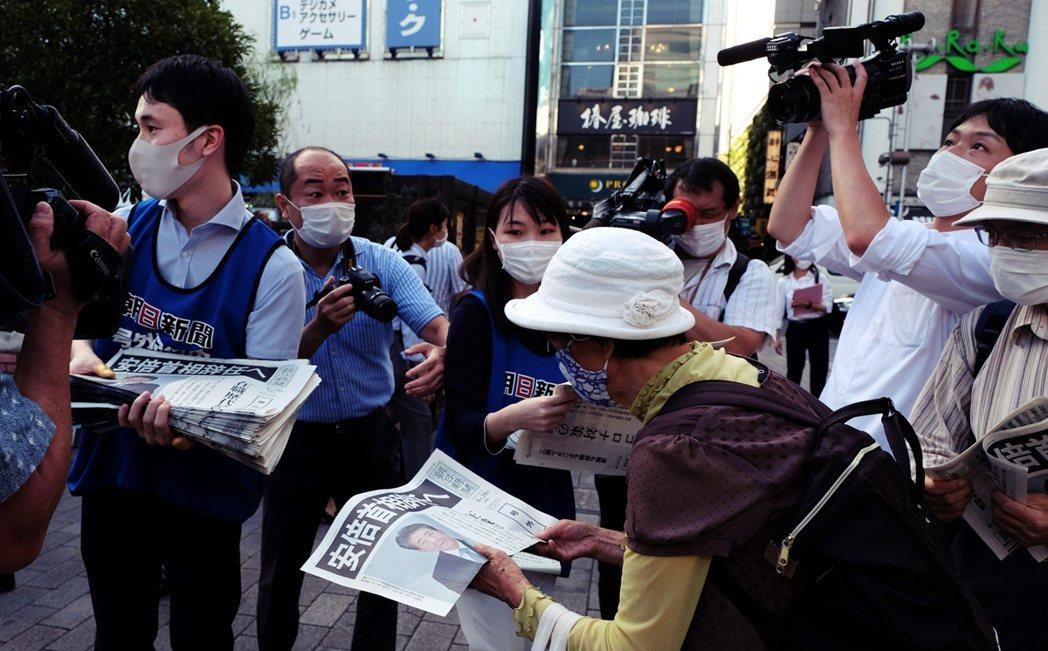 28日派發報紙,安倍欲辭職的消息滿天飛。 圖/法新社