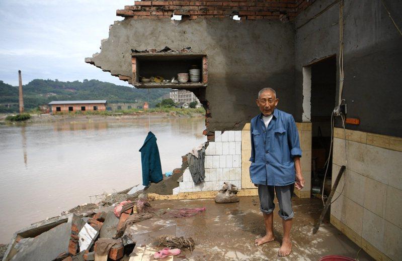 圖為四川省犍為縣孝姑鎮八一村8月19日洪水退去後,一位村民站在遭洪水沖毀的住家內。中新社