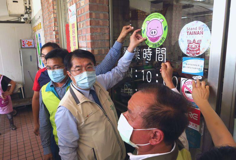 台南市長黃偉哲(中)、台南市議員陳秋宏(右三)、吳通龍(右一)宣導餐飲店家張貼使用國產豬肉標章。圖/台南市政府農業局提供