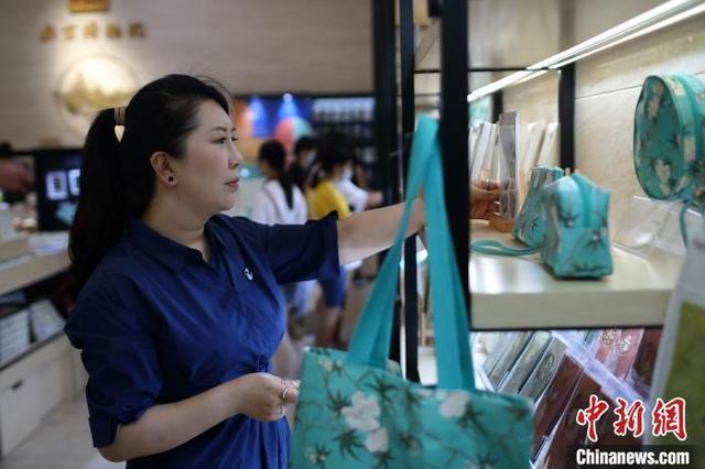 70後台青殷伊玲在整理南京博物院文創店中的商品。圖/中新社