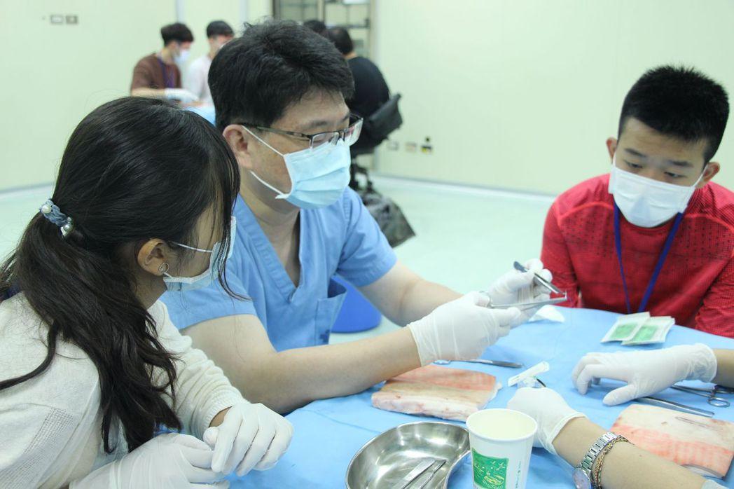 「醫學系」主任梁正隆(中)親自示範豬皮縫合技術,引導高中生基本概念實作。 義大/...