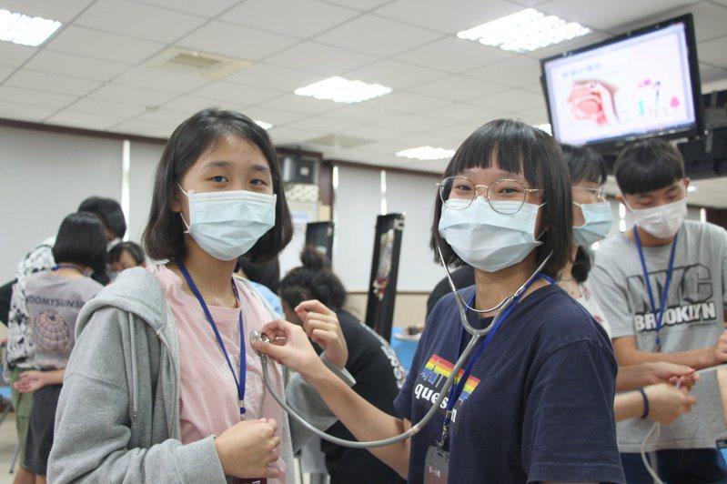 學員練習使用聽筒體驗醫生檢測工作,從中學習知識。圖/義守大學提供