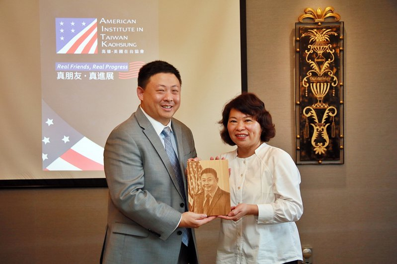美國在台協會高雄分處處長禹道瑞(左)今拜訪嘉義市,市長黃敏惠致贈禹的檜木版畫像。圖/嘉義市府提供
