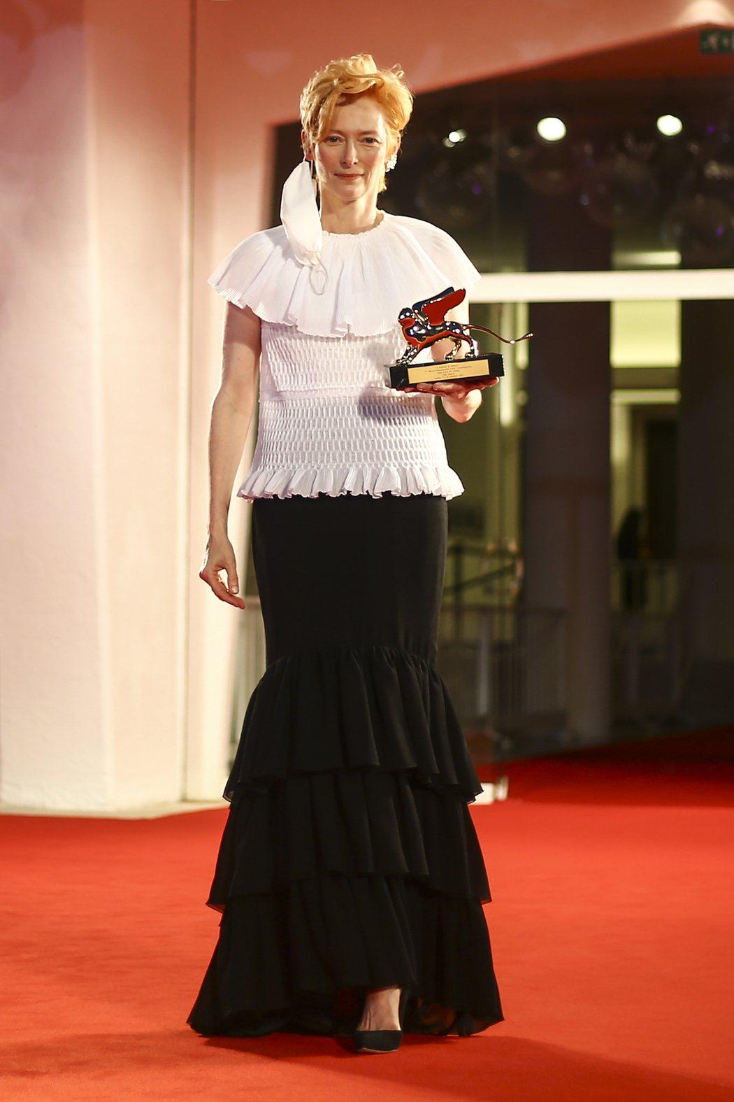 蒂妲史雲頓獲威尼斯影展頒發終身成就獎,拍照時把口罩摘下、垂在臉旁。圖/美聯社