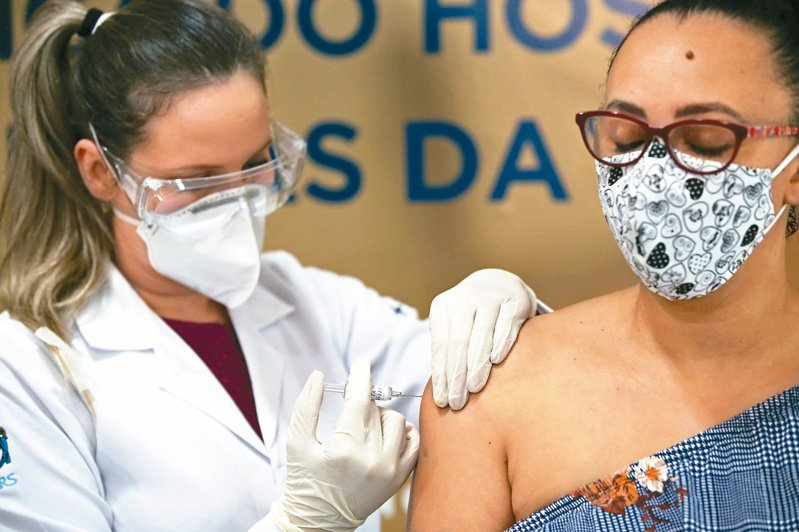 巴西南部城市阿雷格里港一名護理師(左),八月八日為志願者(右)施打試驗中的新冠肺炎疫苗。(路透)