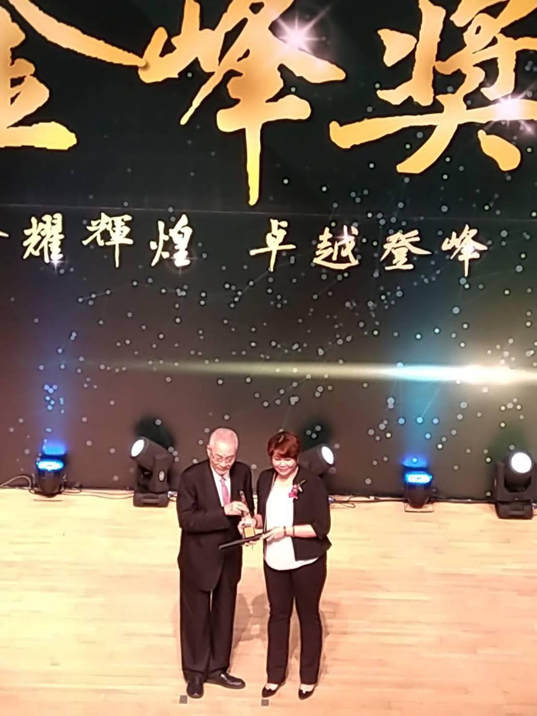 前副總統吳敦義頒給鼎日能源董事長王衣婷金峰獎獎座。 翁永全/攝影