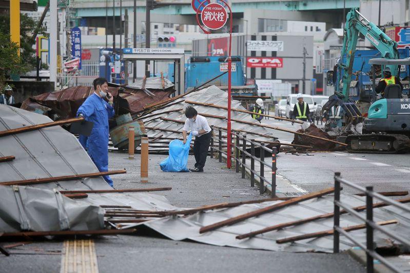 海神颱風襲擊日本留下許多災情。圖為福岡的工作人員正在清理被颱風掃落的鐵皮屋頂。 法新社