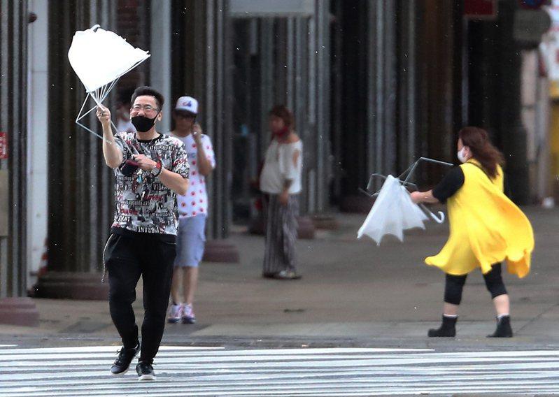 海神來襲 海神颱風6日侵襲日本九州地區,鹿兒島市街頭民眾的雨傘被強風吹壞。(歐新社) 歐新社