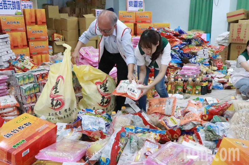 普度期間各地捐助超過2百萬元的普度供品,堆積如山,雲林家扶中心動員志工幫忙分裝發送給受扶戶。記者蔡維斌/攝影