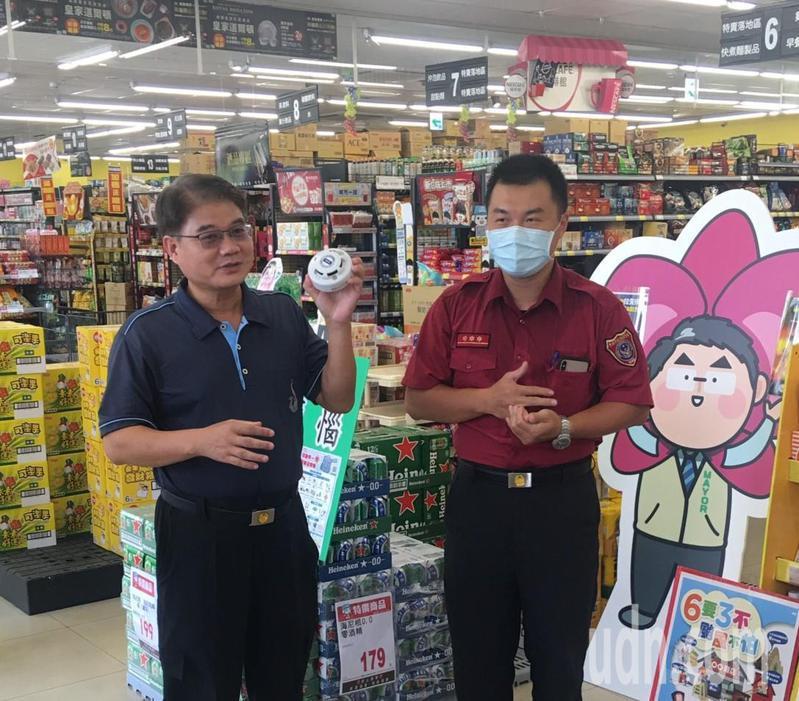 台南市第二消防大隊長丁春能(左)今天到大賣場宣導裝設住警器的重要。 記者吳淑玲/翻攝