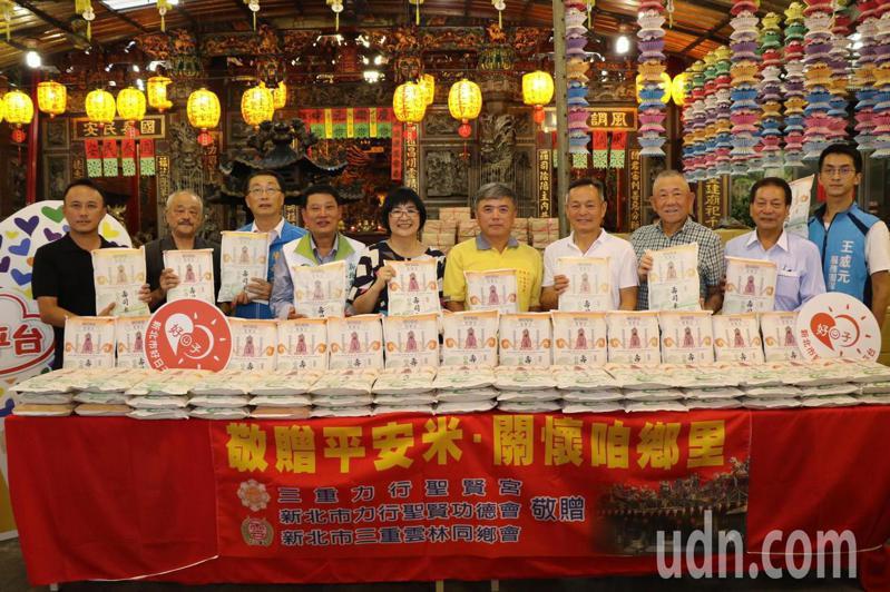 新北市三重力行聖賢宮主委李志能(右五)代表捐贈8000斤平安米, 社會局長張錦麗(右六)代表受贈。記者施鴻基/攝影