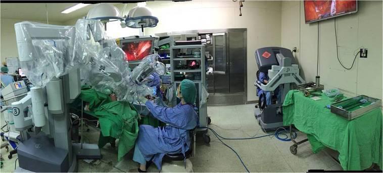 圖二:經口機器手臂手術主刀醫師在遠端操控台操縱手臂,另一位助手還可在病患身旁協助...