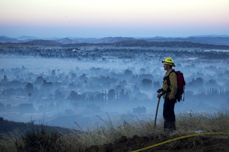 一名消防員在加州一高處看著遠方的山火,反聖嬰現象使西南部更乾燥,火勢更大。美聯社