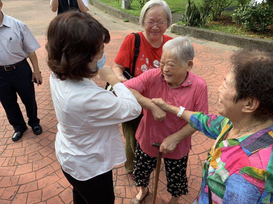 九旬黃姓婦人(右二)與嘉義市長黃敏惠(左一)以碰手肘打招呼,並一同高喊「自己的健...
