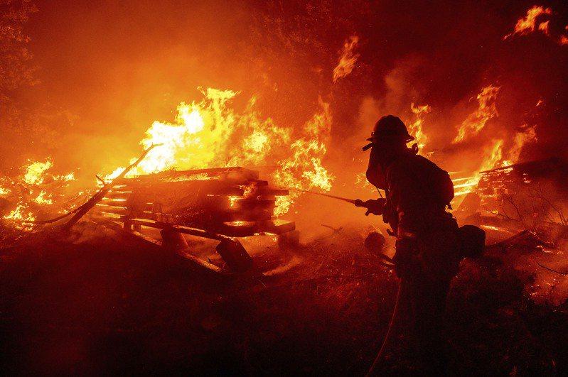 消防隊員正在試圖撲滅吞噬掉房屋的野火。  美聯社