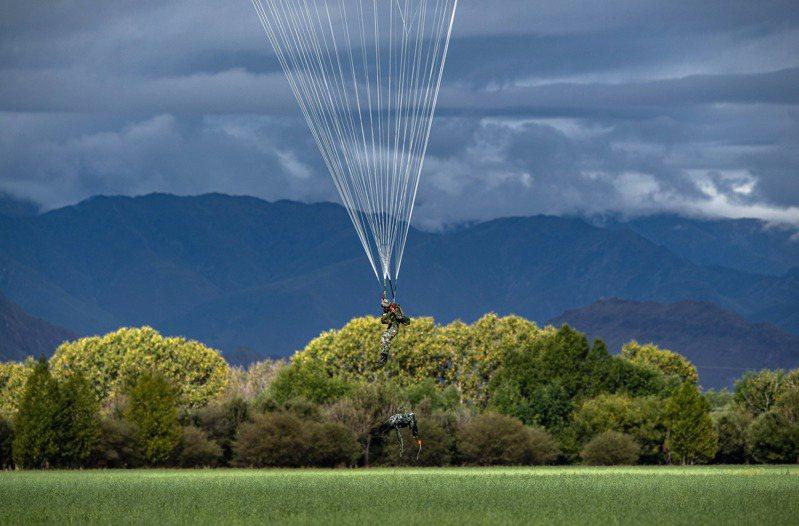解放軍西藏軍區某特戰旅與某陸航旅近日聯合在海拔4000多米的陌生地域完成高原首次低空攜裝傘降訓練。(中新社)