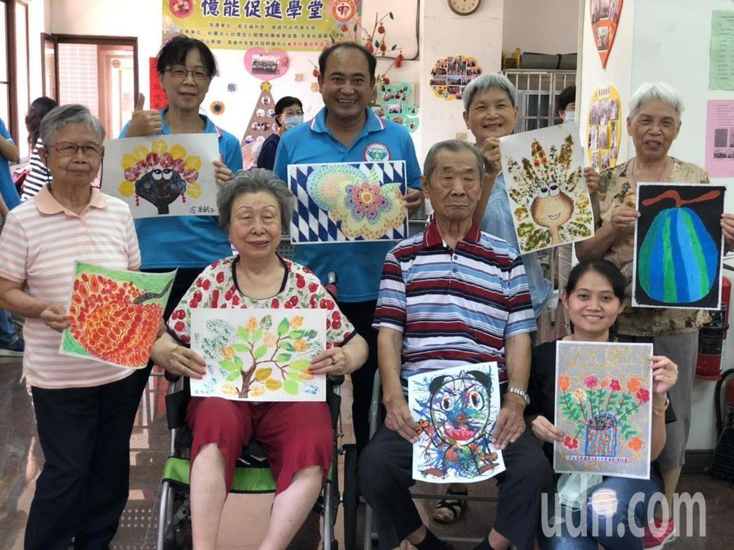 失智社區服務據點的繪畫課程鼓勵長輩展現創作潛能,作品讓協會秘書長林英明(後排左二...