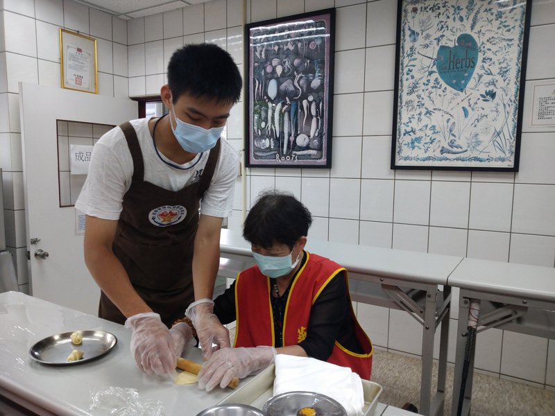 學生們陪伴華山長輩從揉麵糰、桿餅皮、包餡料到將蛋黃酥送進烤爐。圖/明新科大提供