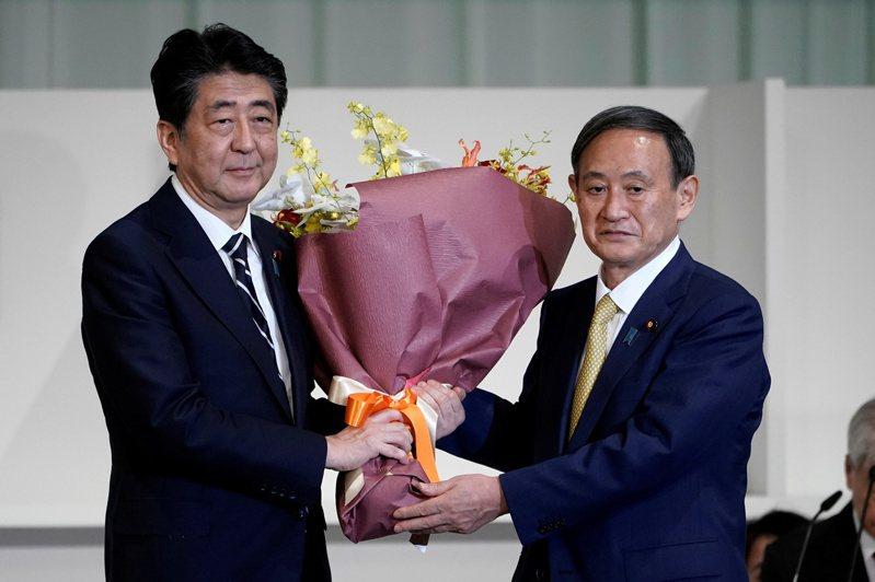 安倍晉三(左)在十四日下午自民黨總裁補選結果出爐後,大力稱讚勝選的菅義偉(右),說他是令和時代最適任的新黨魁。(路透)