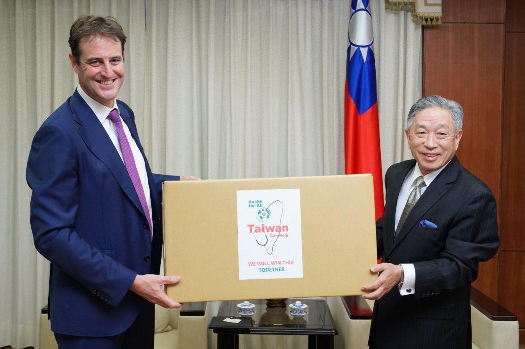 外交部次長田中光(右)代表我國政府捐贈澳方防疫口罩50萬枚,由澳洲辦事處代表高戈...