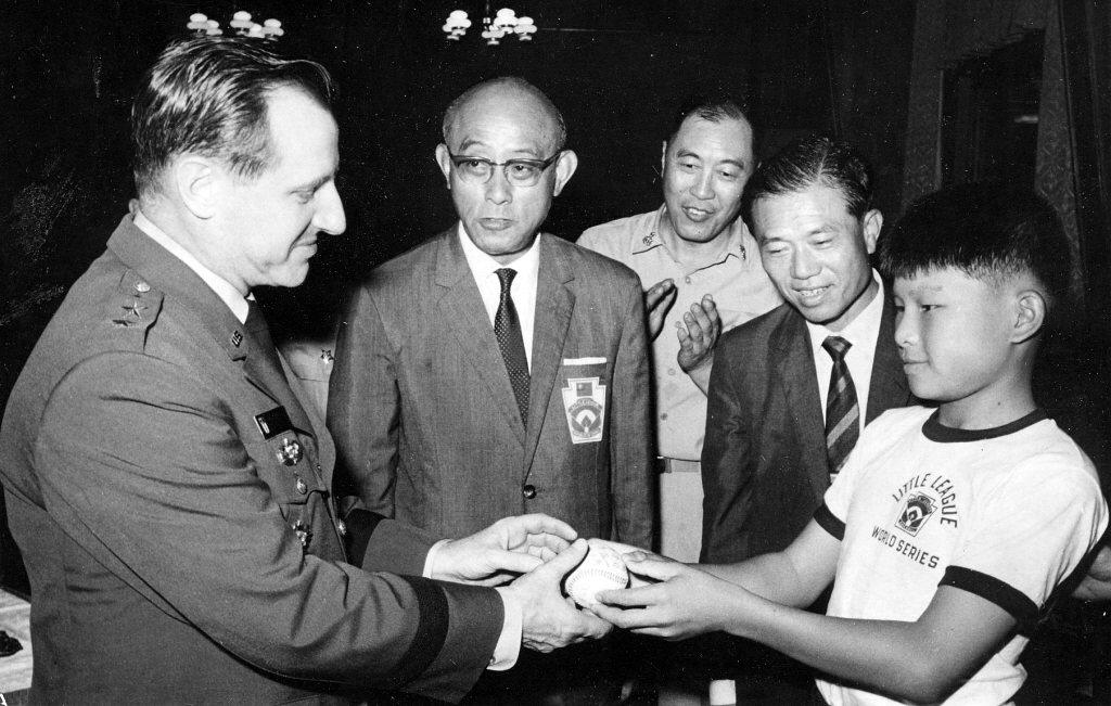 1969年9月8日,金龍少棒隊隊長陳弘丕,將簽名棒球致贈美軍顧問團團長威烈拉少將。 圖/聯合報系資料照