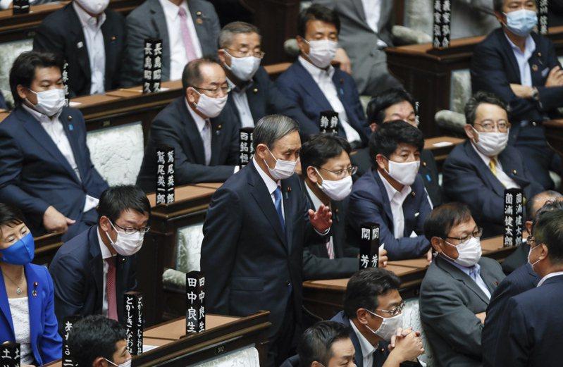 菅義偉(中)16日下午就任日本首相,並公布新閣員名單。歐新社