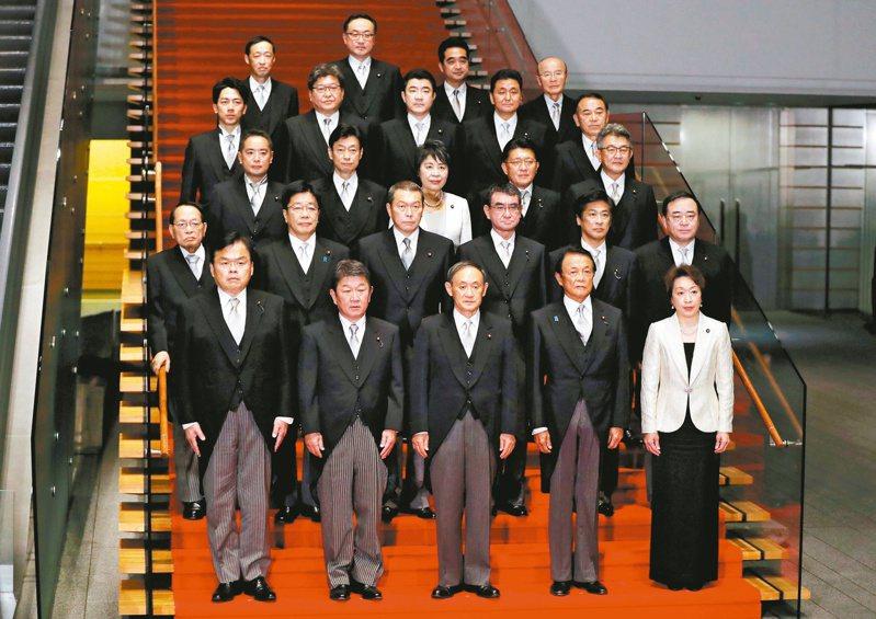 日本首相菅義偉(前排中)十六日率領閣員,在東京首相官邸合照。(路透)