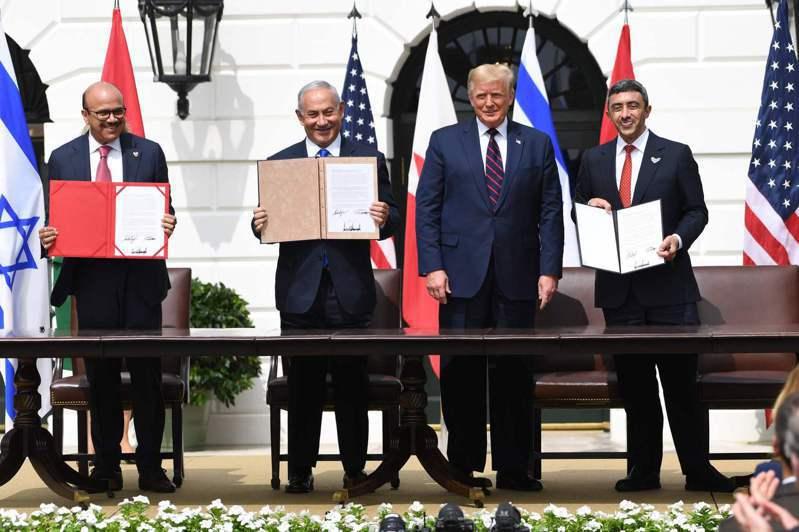 巴林外長札亞尼(左)、以色列總理內唐亞胡(左二)及阿聯外長阿布杜拉(右),十五日在白宮簽署關係正常化協議,美國總統川普(右二)見證簽署儀式。(法新社)