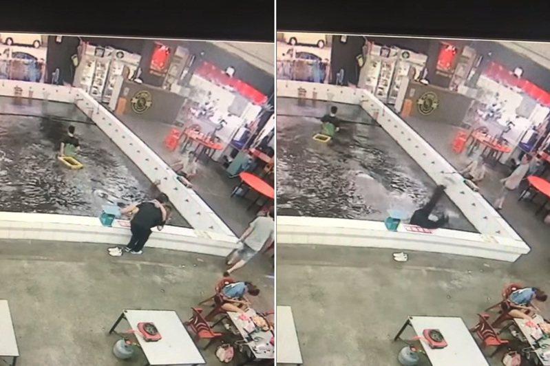 一對情侶於釣蝦池邊「公主抱」,結果重心不穩摔入池中。 圖/翻攝自爆廢公社影片