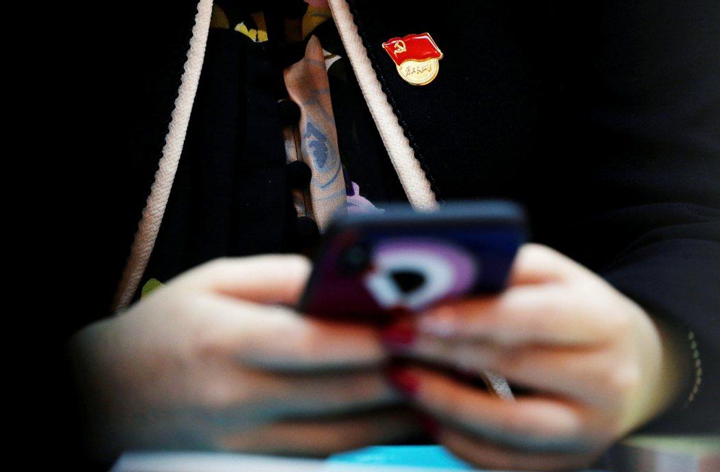 正在使用手機的中國共產黨黨員。 圖/路透社
