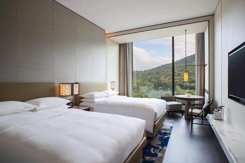 台北士林萬麗酒店鬧中取靜,圖為尊貴山景客房兩中床,綠意入眼。