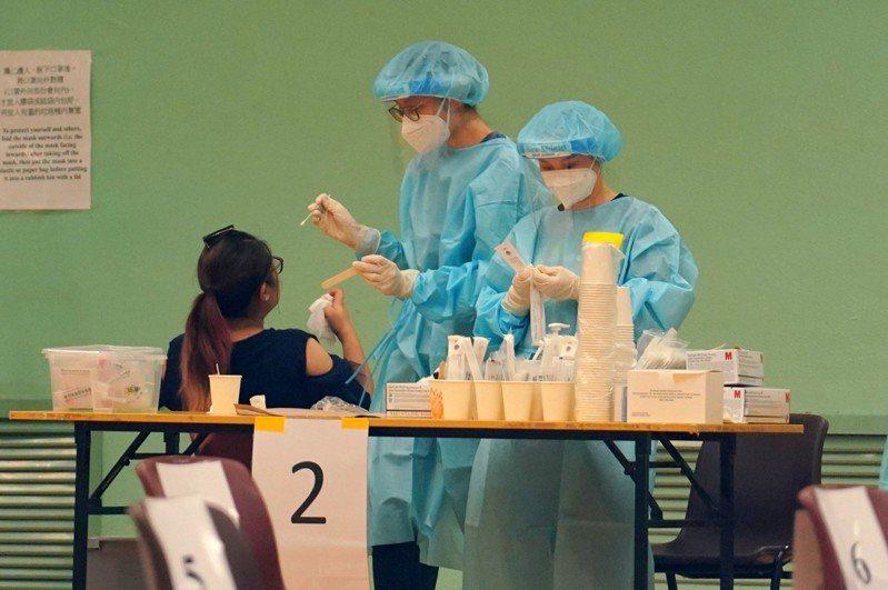 協助香港進行普篩的內地支援隊16日離港,他們共檢測178.3萬個樣本,發現確診病例與隱形患者共42人。圖為醫護人員採檢情形。中新社