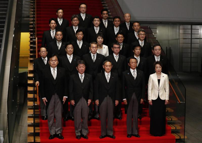 日本首相菅義偉(前排中)16日率領閣員,在東京首相官邸合照。(新華社)